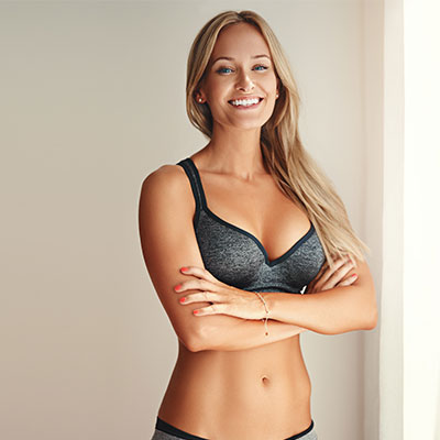 Young and in physical shape woman wearing sports bra crossing her arms | FlexSure